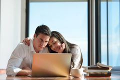 Relaxed young couple working on laptop computer at home Stock Image