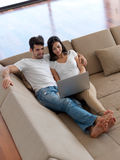 Relaxed young couple working on laptop computer at home. Happy young relaxed  couple working on laptop computer at modern home indoor Stock Photography