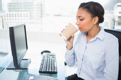Relaxed young dark haired businesswoman drinking coffee Royalty Free Stock Photo