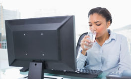 Relaxed young dark haired businesswoman drinking water Stock Photo