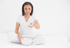 Relaxed young dark haired model eating popcorn Royalty Free Stock Photography