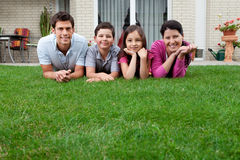 Relaxed young family lying on grass Stock Image