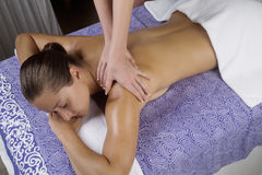 Relaxed young female getting a stone massage in a spa Royalty Free Stock Images