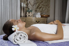 Relaxed young female getting a stone massage in a spa Royalty Free Stock Image