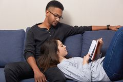 Relaxed young female lies on knees of her dark skinned boyfriend, reads romantic story, pose together at couch, enjoys calm. Domestic atmosphere and spare royalty free stock image