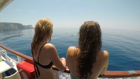 Relaxed young female tourists friends traveling on a sailboat looking the sea and summer sunny day -. Relaxed young female tourists friends traveling on a stock video footage