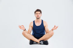 Relaxed young fitness man sitting in lotus pose and meditating Royalty Free Stock Image