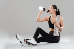 Relaxed young fitness woman with towel sitting and drinking water Royalty Free Stock Images