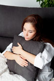 Relaxed young girl hugging a cushion Royalty Free Stock Photos
