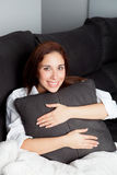 Relaxed young girl hugging a cushion Royalty Free Stock Photo