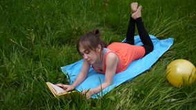 Relaxed young girl reading the book in the field. Cute teen lying on the grass. Video footage HD shooting of static. Relaxed young girl reading the book in stock video footage