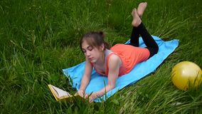Relaxed young girl reading the book in the field. Cute teen lying on the grass. Video footage HD shooting of static. Relaxed young girl reading the book in stock footage