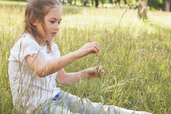 Relaxed young girl sitting in field Stock Photo