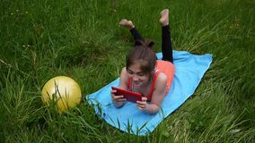 Relaxed young girl using digital tablet in country field. Cute teen lying on the grass. Video footage HD shooting of. Relaxed young girl using digital tablet in stock footage
