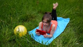 Relaxed young girl using digital tablet in country field. Cute teen lying on the grass. Video footage HD shooting of. Relaxed young girl using digital tablet in stock video