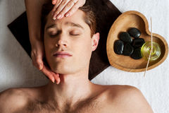 Relaxed young guy getting a face massage Royalty Free Stock Photos