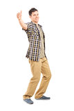 Relaxed young guy giving a thumb up Stock Images