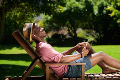 Relaxed young guy listening to music on digital tablet Royalty Free Stock Photos