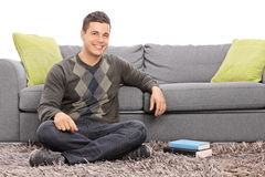 Relaxed young guy sitting on the floor Royalty Free Stock Images