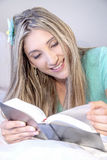 Relaxed young lady reading Stock Image