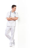 Relaxed young male nurse lean on the wall Royalty Free Stock Images