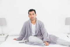 Relaxed young man in bathrobe sitting on bed Stock Photography