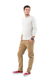 Relaxed young man in beige pants and gray shirt smiling looking back over shoulder Stock Photography