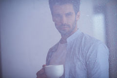 Relaxed young man drink first morning coffee withh rain drops on Stock Photos