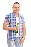 Relaxed young man holding a bottle of beer Royalty Free Stock Images