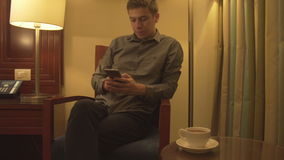 Relaxed young man holding the phone typing message stock video