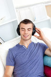 Relaxed young man listening to music on the couch Royalty Free Stock Photo