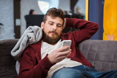 Relaxed young man lying on sofa and using cellphone. Relaxed young handsome attractive man lying grey on sofa and using cellphone Royalty Free Stock Image