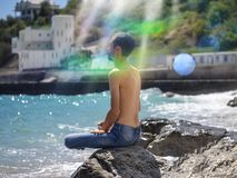Relaxed young man meditating while sitting on the beach stock images