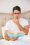 Relaxed young man reading book in bed. At house Royalty Free Stock Images