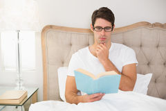 Relaxed young man reading book in bed. At house Stock Image