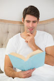 Relaxed young man reading book in bed. At house Stock Photos