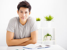 Relaxed young man reading  book in living room Stock Image