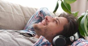 Happy man singing while listening music on headphones stock video footage