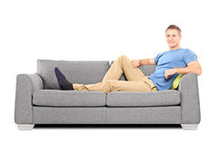 Relaxed young man sitting on a comfortable sofa. Isolated on white background Royalty Free Stock Photos