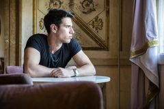 Relaxed Young Man Sitting Comfortably at Table Royalty Free Stock Photography