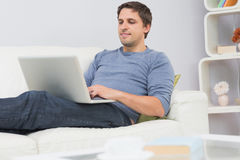 Relaxed young man using laptop in living room Stock Photography