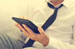 Relaxed young man using a tablet computer. A relaxed young man with his necktie loosened using a tablet computer Stock Images