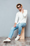Relaxed young man in white shirt, jeans, hat and sunglasses Royalty Free Stock Photos