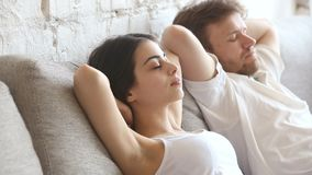 Relaxed young man and woman resting leaning on comfortable sofa stock video footage