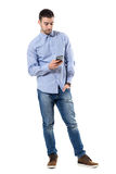 Relaxed young smart casual business man typing message on mobile phone. Full body length portrait isolated over white background Royalty Free Stock Photography