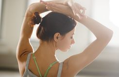 Relaxed young sportswoman doing yoga and meditating in studio Royalty Free Stock Image
