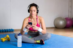 Restful girl. Relaxed young sportswoman with headphones and smartphone listening to music from playlist between workouts Royalty Free Stock Photo