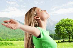 Relaxed young woman with arms outstretched Stock Photo