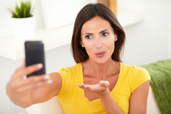 Relaxed young woman blowing a kiss Stock Photography
