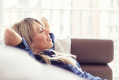 Relaxed young woman on couch. Relaxed young woman lying on couch in living room Royalty Free Stock Photo